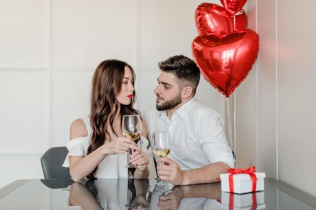 Heureux bel homme et femme boivent du vin blanc à la maison avec un cadeau dans une boîte cadeau et des ballons en forme de coeur rouge à la maison