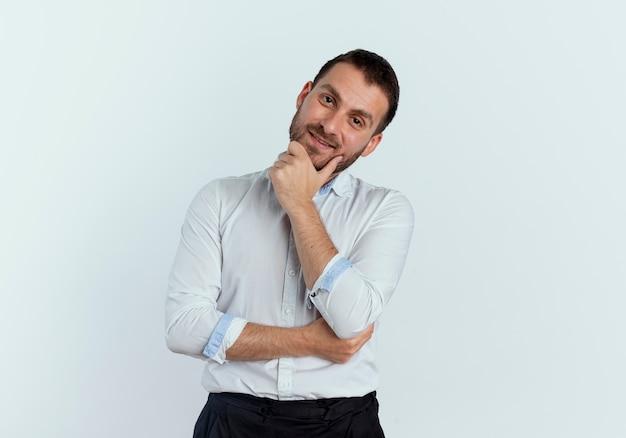 Heureux bel homme met la main sur le menton isolé sur un mur blanc