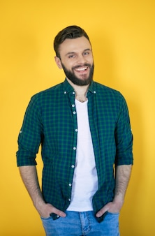 Heureux bel homme moderne barbu excité dans la chemise à carreaux pose avec un large sourire à pleines dents