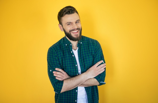Heureux bel homme moderne barbu excité dans la chemise à carreaux pose