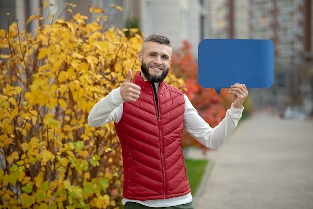 Heureux bel homme montrant le geste ok tout en tenant une pancarte dans sa main