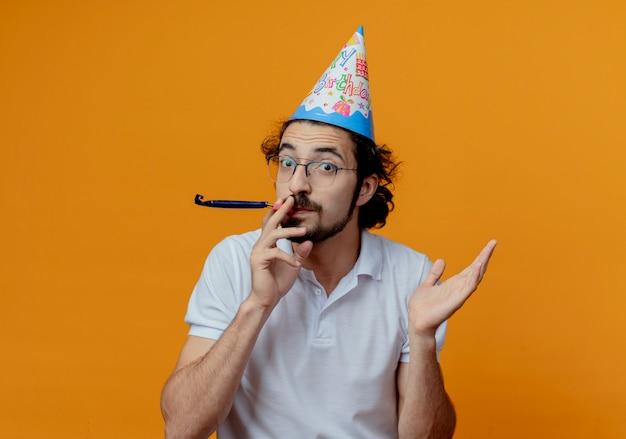 Heureux bel homme portant des lunettes et chapeau d'anniversaire soufflant sifflet propagation main isolé sur fond orange