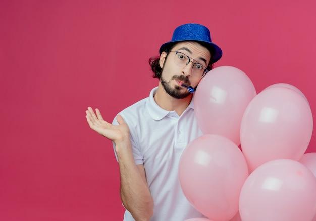 Heureux bel homme portant des lunettes et un chapeau bleu tenant des ballons soufflant sifflet et répandre la main isolée sur fond rose avec espace de copie
