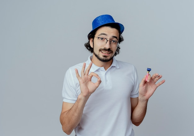 Heureux bel homme portant des lunettes et un chapeau bleu tenant un sifflet et montrant le geste okey isolé sur fond blanc