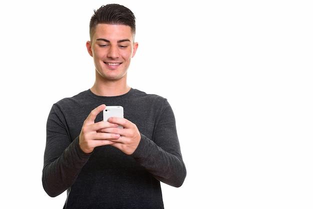 Heureux bel homme souriant tout en utilisant pho mobile