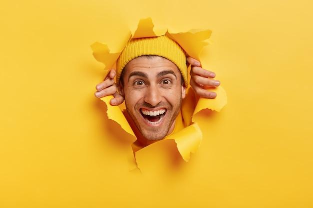 Heureux bel homme avec sourire à pleines dents, expression joyeuse, mur de papier de larmes