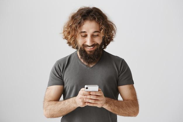 Heureux bel homme textos sur smartphone, regardant le téléphone mobile ravi