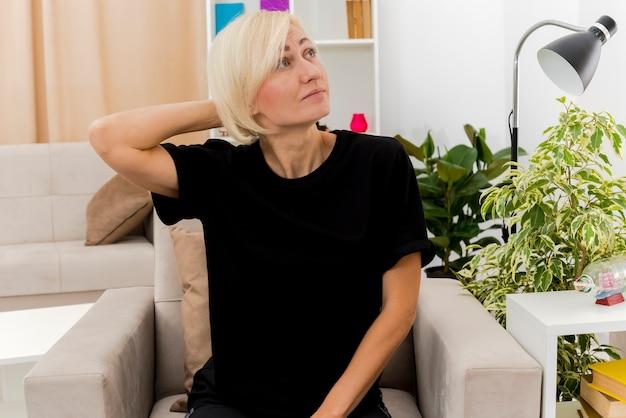 Heureux belle femme russe blonde est assise sur un fauteuil mettant la main sur la tête derrière en regardant sur le côté à l'intérieur du salon