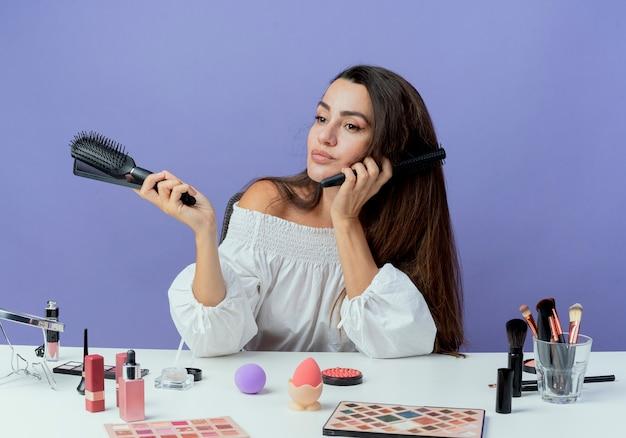 Heureux belle fille est assise à table avec des outils de maquillage détient des peignes à cheveux à côté isolé sur mur violet