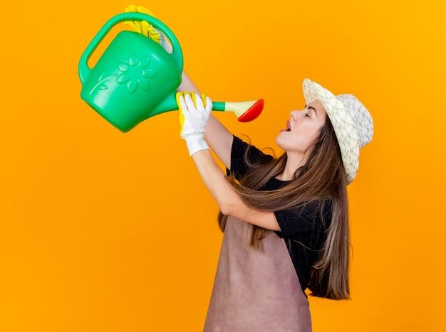 Heureux belle fille de jardinier en uniforme et chapeau de jardinage avec des gants s'abreuvant avec arrosoir isolé sur fond orange