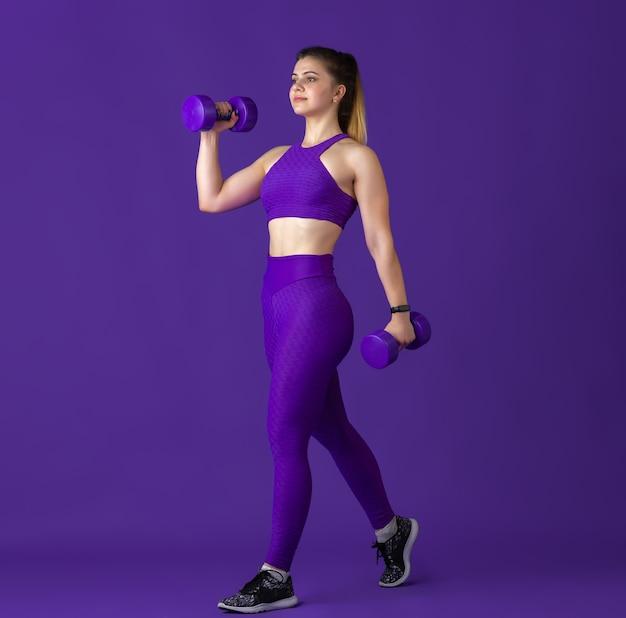 Heureux. belle jeune athlète féminine pratiquant, portrait violet monochrome. modèle caucasien de coupe sportive avec poids. musculation, mode de vie sain, concept de beauté et d'action.