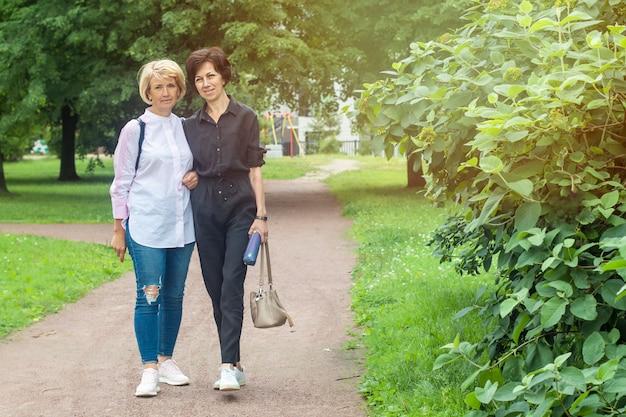 Heureux belles dames, couple lgbt de femmes adultes matures amoureuses marchant dans le parc, se tenant la main.