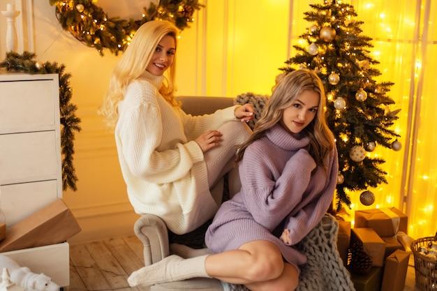 Heureux belles jeunes copines avec le sourire en pull vintage tricoté s'asseoir dans un fauteuil près de l'arbre de noël et des lumières jaunes