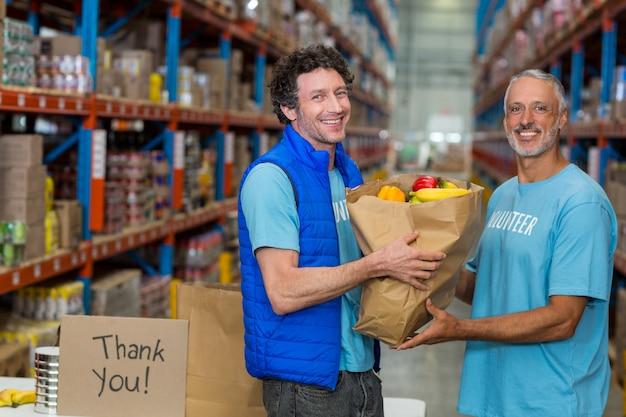 Heureux bénévoles tenant un sac d'épicerie et regardant la caméra