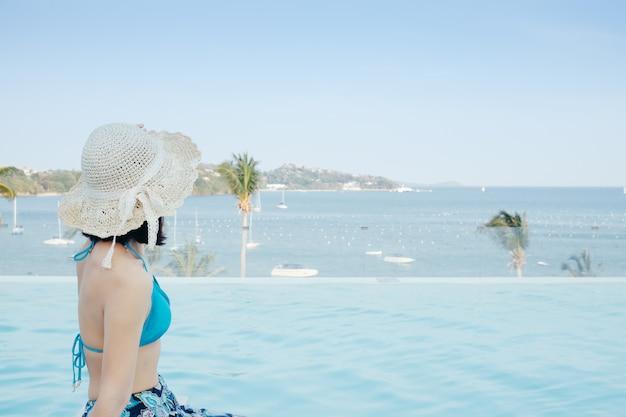 Heureux bikini femme sur la piscine et la mer nuages ciel.
