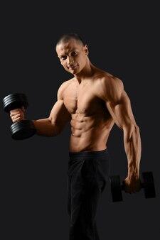 Heureux bodybuilder masculin exerçant avec des haltères souriant sur fond noir