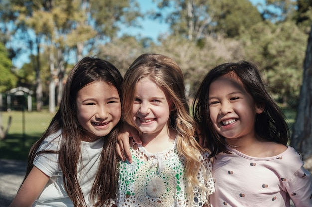 Heureux et en bonne santé, mélange de jeunes filles ethniques, embrassant et souriant dans le parc, meilleurs amis et amitié