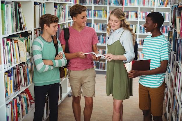 Heureux camarades de classe qui étudient dans la bibliothèque