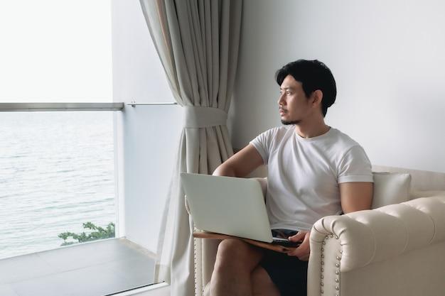 Heureux sur le canapé avec vue sur la mer et concept de travail staycation