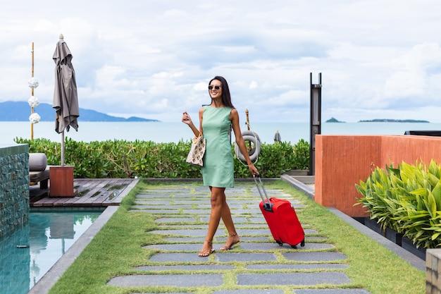 Heureux caucasien jolie femme touristique élégante de cheveux longs en robe avec valise rouge à l'extérieur de l'hôtel