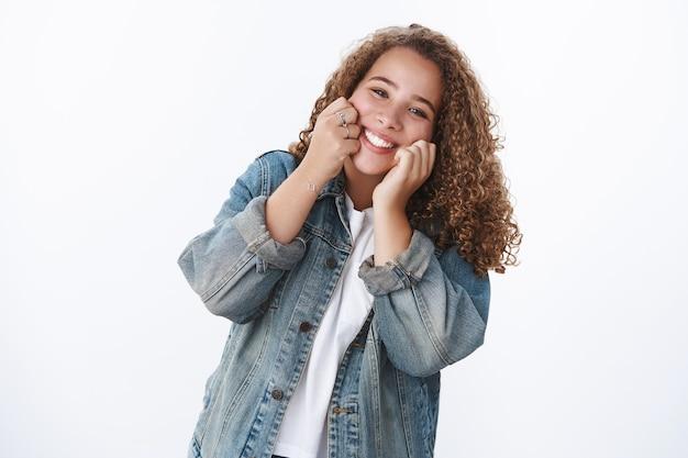 Heureux charismatique tendre idiot joufflu jolie fille touchant les joues souriant joyeusement avoir le meilleur jour profiter de la vie en s'amusant à bien faire debout veste en jean mur blanc s'amuser en imitant
