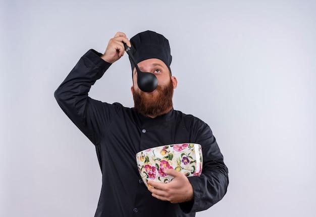 Un heureux chef barbu homme en uniforme noir, boire de la soupe avec une louche d'énorme tasse florale sur un fond blanc