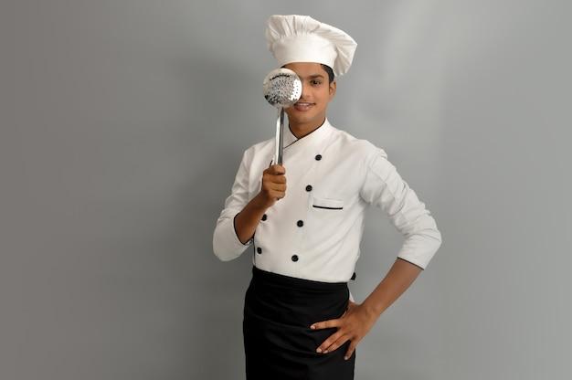 Heureux chef masculin vêtu d'un uniforme tenant une écumoire en acier sur un œil