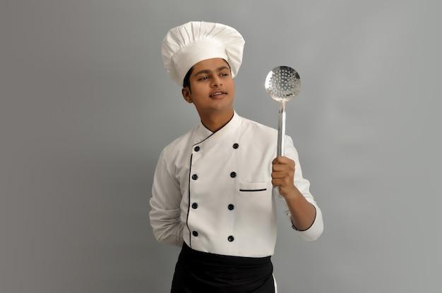Heureux chef masculin vêtu d'un uniforme tenant un skimmer en acier et regardant