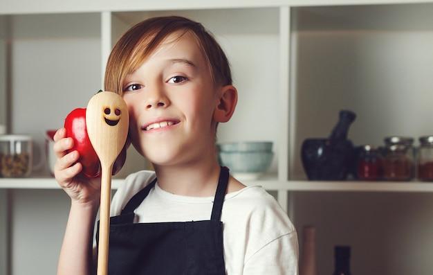 Heureux chef tenant une cuillère en bois. enfant portant un tablier de chef. concept de cuisine de cuisine.