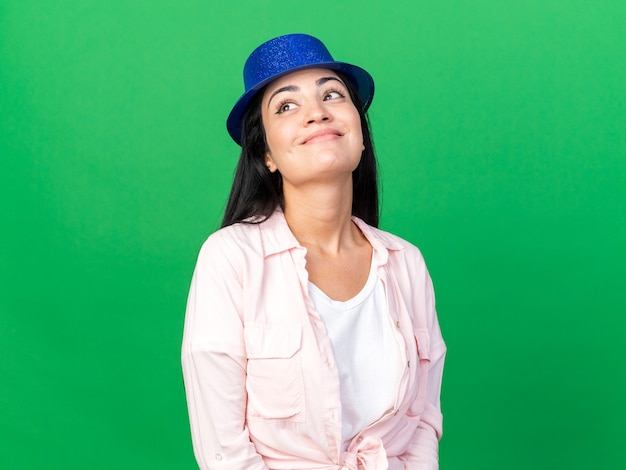 Heureux de chercher une belle jeune femme portant un chapeau de fête isolé sur un mur vert