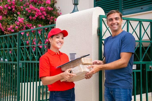 Heureux client masculin recevant un formulaire de commande courrier féminin en uniforme rouge. enthousiaste livreuse brune livrant des boîtes et debout à l'extérieur. service de livraison express et concept d'achat en ligne