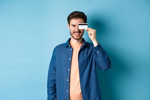 Heureux client masculin tenant une carte de crédit en plastique sur les yeux et souriant, debout en tenue décontractée sur fond bleu.