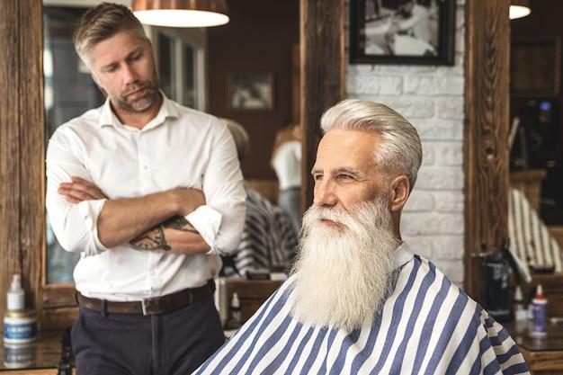Heureux coiffeur et son client dans le salon de coiffure