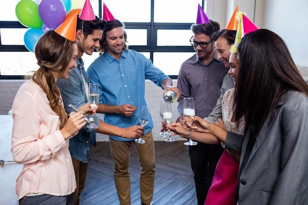 Heureux collègue servant des coupes de champagne pour l'anniversaire