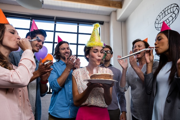 Heureux collègue soufflant des bougies pour l'anniversaire