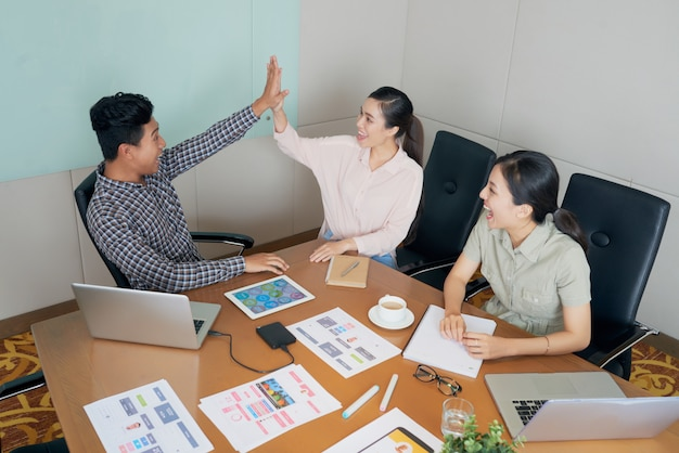 Heureux collègues asiatiques créatifs assis au bureau dans le bureau et faire high-five