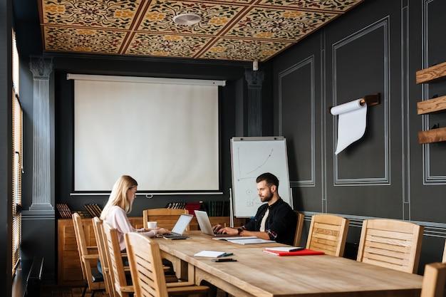 Heureux collègues assis près du café tout en travaillant avec des ordinateurs portables