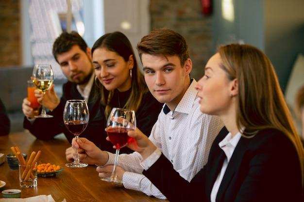 Heureux collègues célébrant lors d'une fête d'entreprise et d'un événement d'entreprise. jeunes caucasiens en tenue d'affaires applaudissant, riant. concept de culture de bureau, travail d'équipe, amitié, vacances, week-end.
