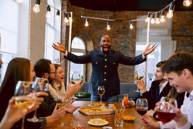 Heureux collègues célébrant lors d'une fête d'entreprise, d'un événement d'entreprise. jeunes caucasiens en tenue d'affaires parlant, buvant du vin. concept de culture de bureau, travail d'équipe, amitié, vacances, week-end.