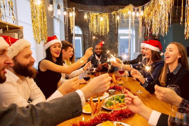 Heureux collègues célébrant pendant la fête de l'entreprise pour le nouvel an et noël