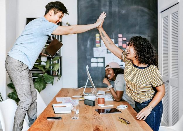 Heureux collègues divers dans une entreprise en démarrage faisant un high five