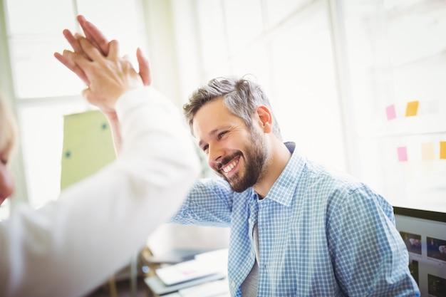 Heureux collègues donnant un high-five dans le bureau créatif