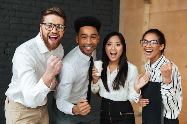 Heureux collègues de jeunes entrepreneurs excités font le geste du gagnant.