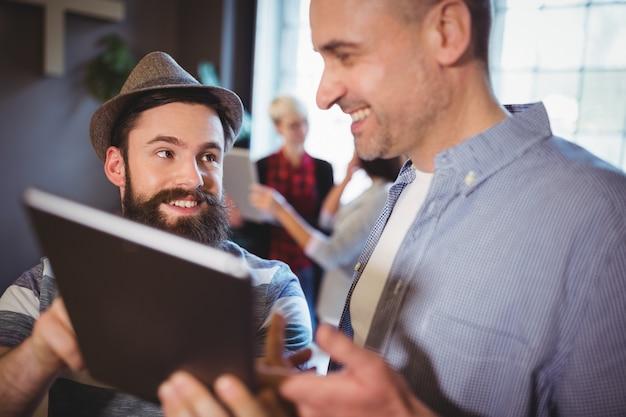 Heureux collègues masculins discutant sur tablette numérique