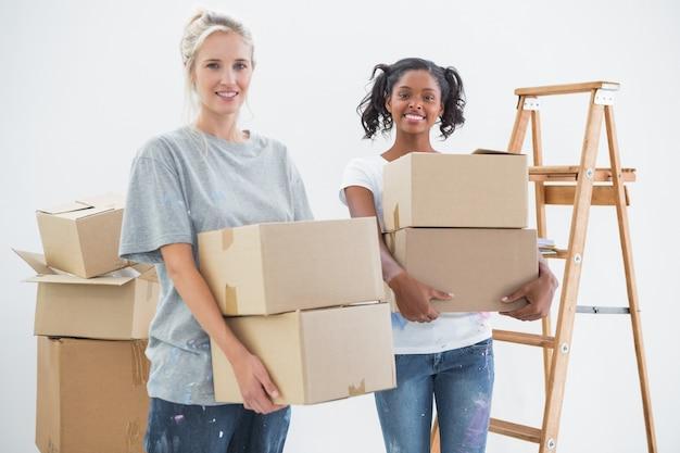 Heureux colocataires portant des boîtes de déménagement