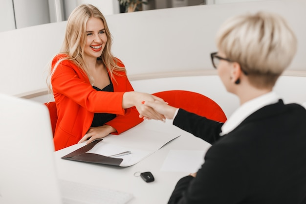 Heureux concessionnaire serrer la main avec le client après accord.