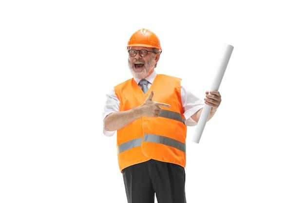 L'heureux constructeur dans un gilet de construction et un casque orange souriant au studio. spécialiste de la sécurité, ingénieur, industrie, architecture, gestionnaire, profession, homme d'affaires, concept d'emploi