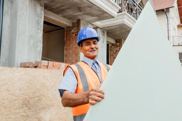 Heureux constructeur debout à l'extérieur derrière un carton vide avec un espace de texte pour copie la construction d'une maison de constructeur en bois porte des planches sur le chantier de construction