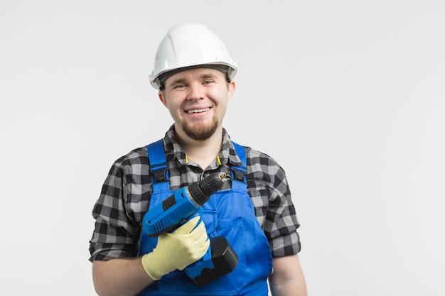 Heureux constructeur mâle caucasien avec un tournevis sur un mur blanc, portant un casque blanc.