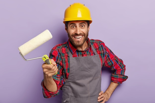 Heureux contremaître attrayant prêt pour la réparation de la maison, tient le rouleau à peinture, décore les murs, porte un couvre-chef de protection jaune, une chemise à carreaux et un tablier, sourit positivement. homme avec outil de construction